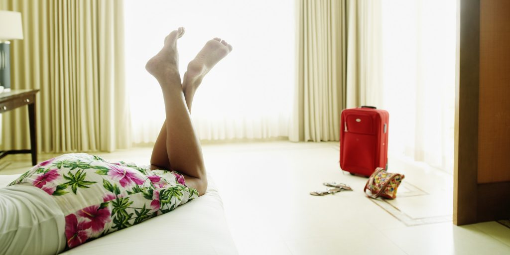 Woman lying on bed in hotel room legs crossed mid section