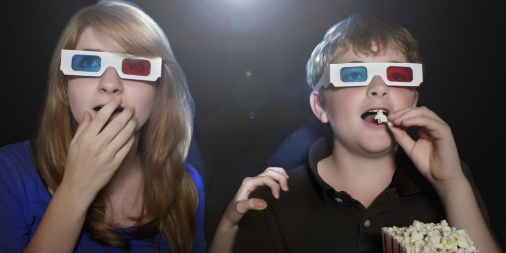 Boy and girl watching 3-D movie eating popcorn