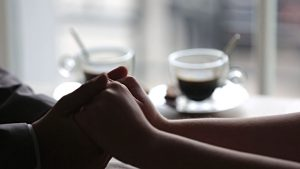 stock-video-89251957-romantic-couple-tenderly-holding-hands-cups-of-hot-coffee-on-background