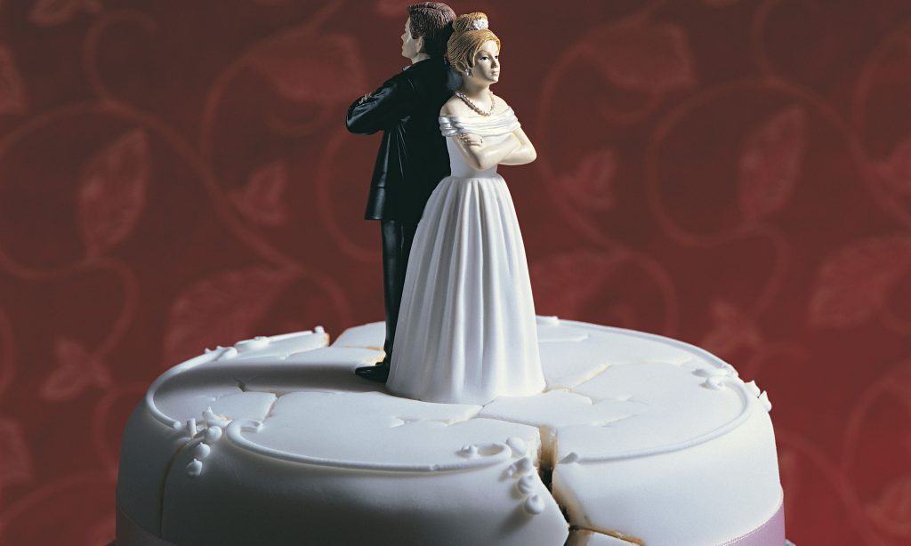 Wedding cake couple standing back to back, arms folded
