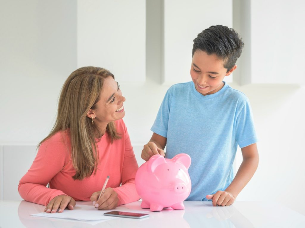 Mother saving for her boy's education in a piggybank - home finances concepts