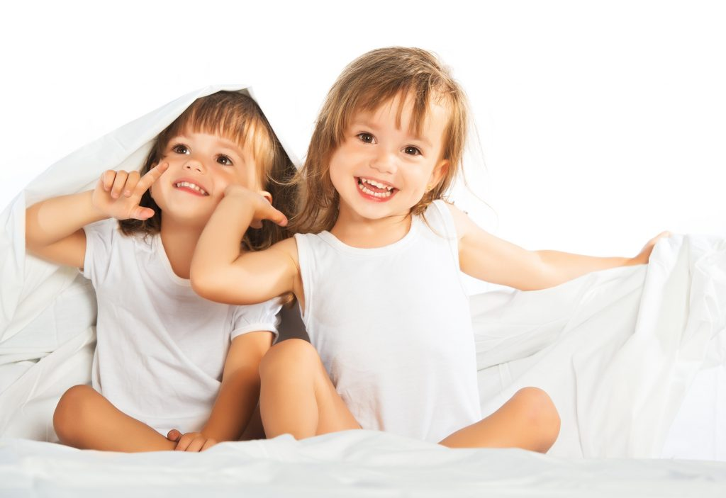 happy little girls twins sister in bed under the blanket having fun, smiling