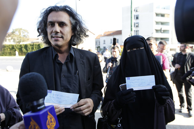 Hind Ahmas (R) wears a niqab despite a nationwide ban on the Islamic face veil and displays a cheque of 120 euros to pay a fine after she was arrested for wearing the niqab in public last May, as she arrives at the courts in Meaux, east of Paris, September 22, 2011. French property developer Rachid Nekkaz (L) who holds the cheque to pay the fine of a second woman who was not present. REUTERS/Charles Platiau (FRANCE - Tags: POLITICS RELIGION CRIME LAW)