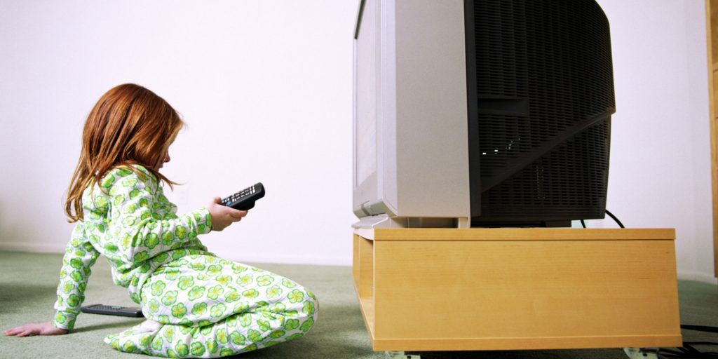 Girl (6-8) in front of television holding remote control, profile