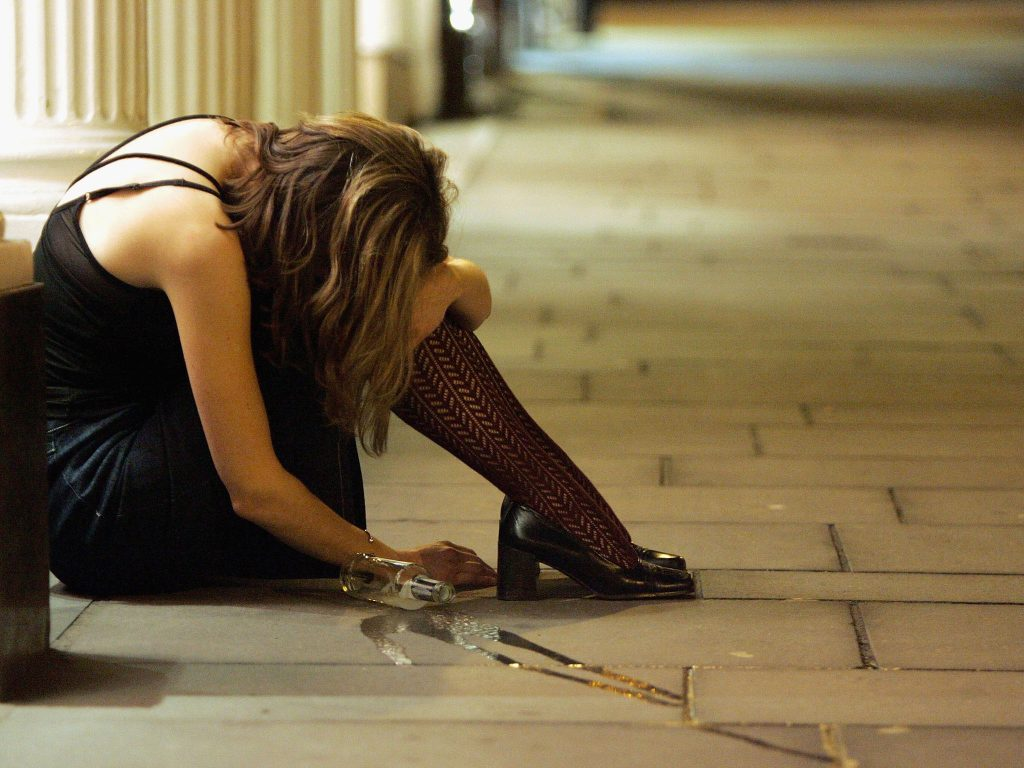 BRISTOL, ENGLAND - FEBRUARY 5: A woman drinker slumps on teh pavement February 5 2005, Bristol, England. This weekend was the last one before pubs and clubs can apply for extended licences. From February 7, venues can begin applying for 24-hour licences, however, the licences will not become effective until the Government puts an order before Parliament in November. Critics fear this will lead to increased binge-drinking, crime, disorder and city centres becoming no-go areas. (Photo by Matt Cardy/Getty Images)