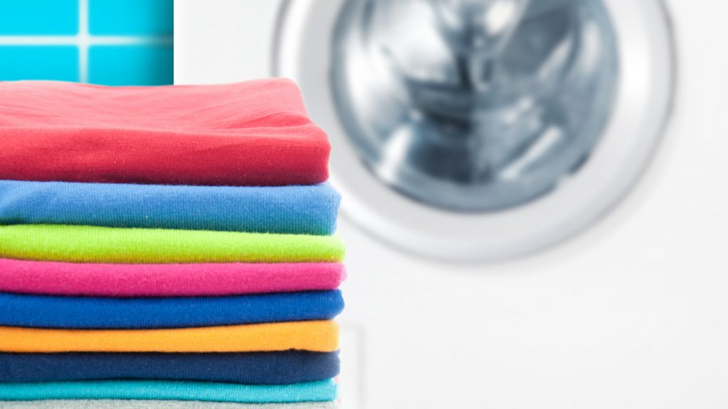 Should you wash new clothes before you wear them? Pile of colorful clothes with washing machine.; Shutterstock ID 226661083; PO: new-clothes-wash-before-wear-today-tease-150519; Client: TODAY digital