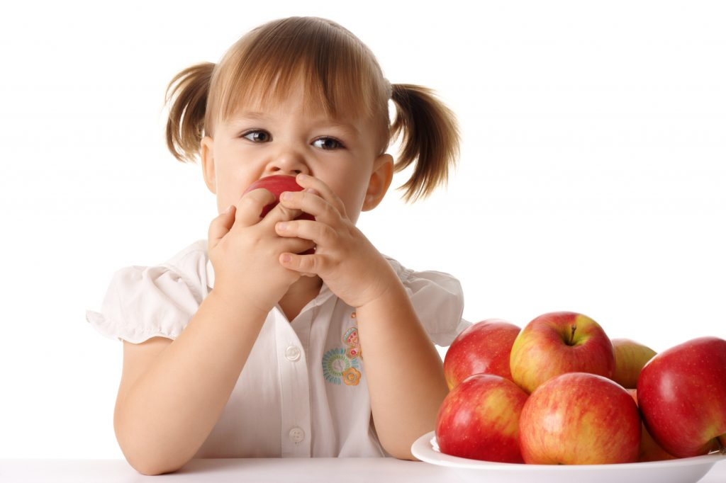 Child eats red apple