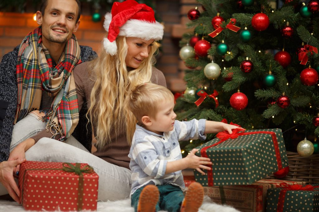 Little boy with parents among New Year gifts under Christmas tree