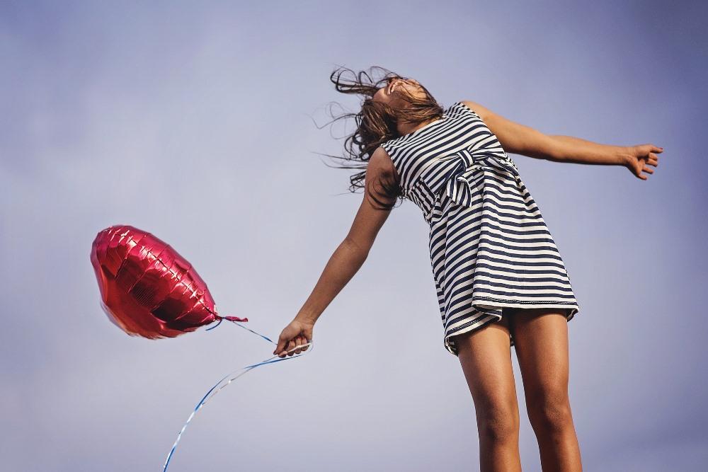 nasmejana-devojka-drži-crveni-balon
